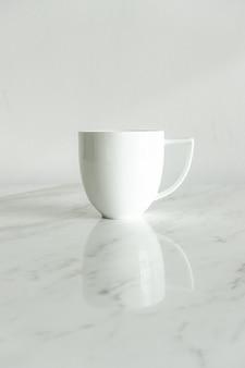Witte koffiekopje op marmeren tafel