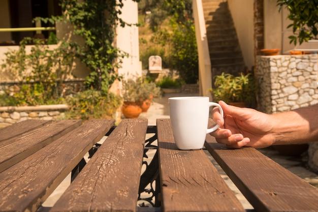 Witte koffiekopje op tafel met buitenomgeving