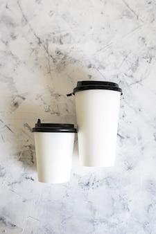Witte koffiekopjes op marmeren tafel