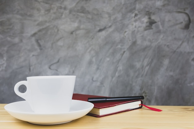 Witte koffiemok en notitieblok op houten tafel