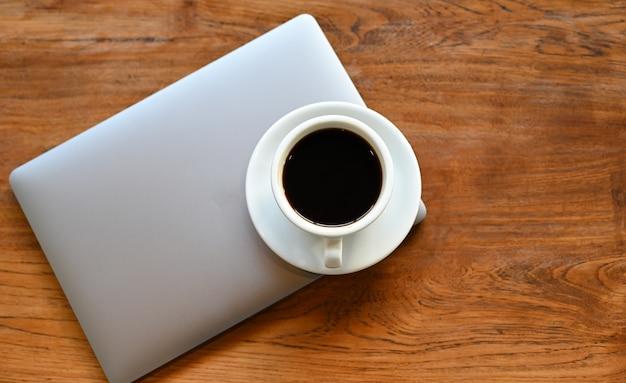 Witte koffiemok geplaatst op de laptop op een houten tafel.