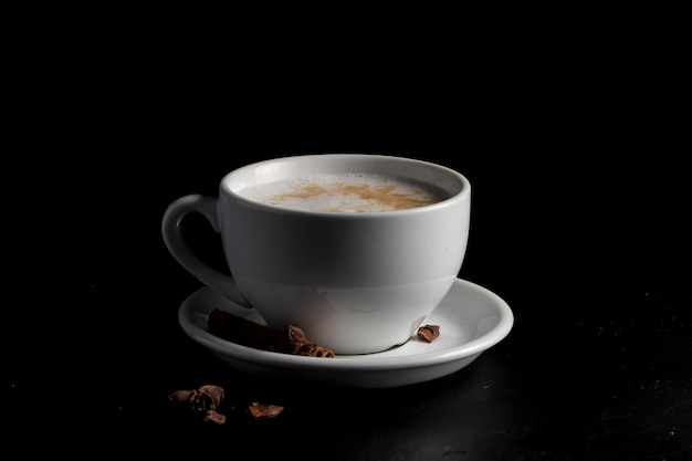 Witte koffiemok met pittige rafkoffie en steranijs op een schotel