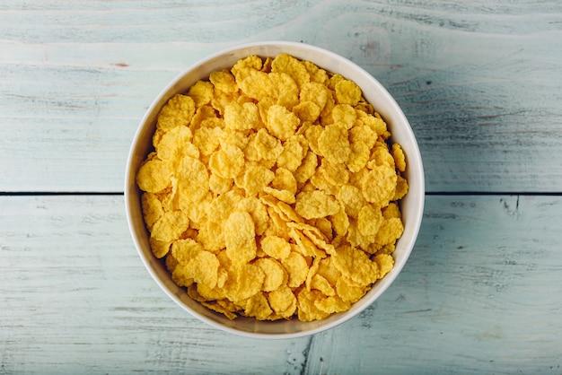 Witte kom cornflakes op een houten ondergrond