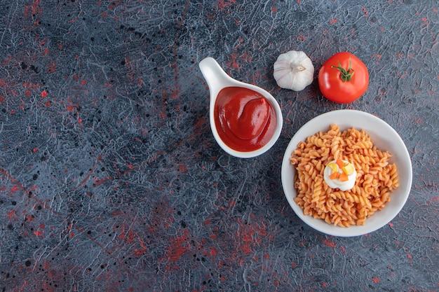 Witte kom heerlijke fusilli pasta op marmeren achtergrond.