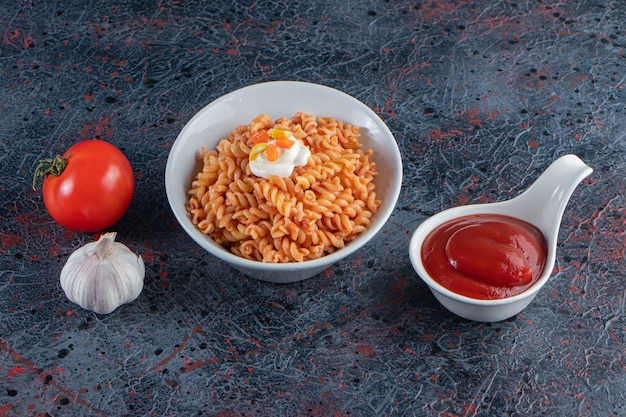 Witte kom heerlijke fusilli pasta op marmeren oppervlak.
