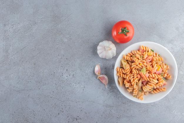 Witte kom heerlijke fusilli pasta op stenen achtergrond.