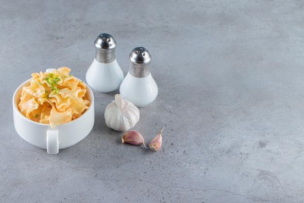 Witte kom heerlijke macaroni met knoflook en zout op stenen achtergrond.