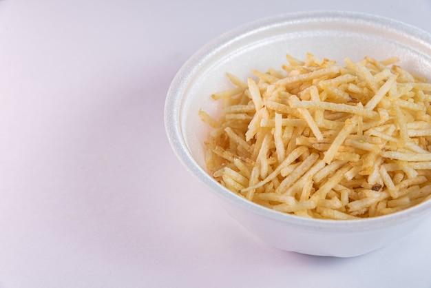 Witte kom met aardappelstro op witte achtergrond