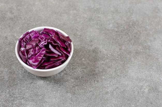 Witte kom met gehakte paarse kool op stenen tafel.