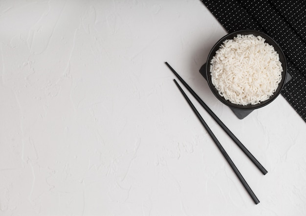 Witte kom met gekookte biologische basmati jasmijnrijst met zwarte stokjes op bamboe
