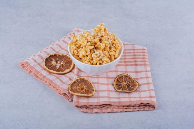 Witte kom met harde snoepjes met noten en schijfjes citroen op steen.