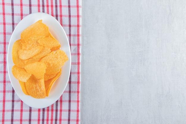 Witte kom met pittige chips op steen geplaatst.