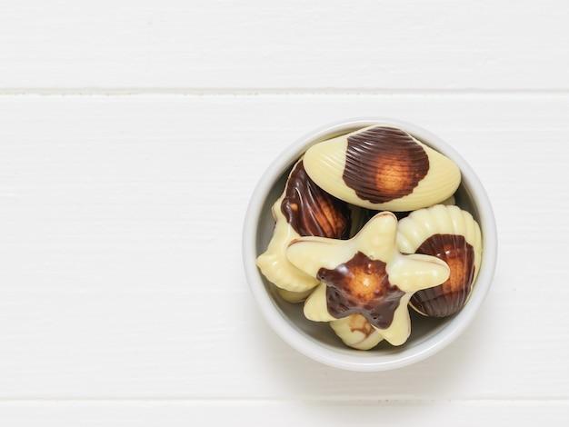Witte kom met snoep in de vorm van zeeschelpen op een witte houten tafel. de zoetheid van melkchocolade. het uitzicht vanaf de top. plat leggen.