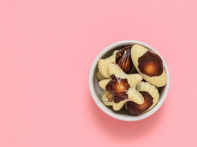 Witte kom met snoepjes in de vorm van zeeschelpen. de zoetheid van melkchocolade. het uitzicht vanaf de top. plat leggen.