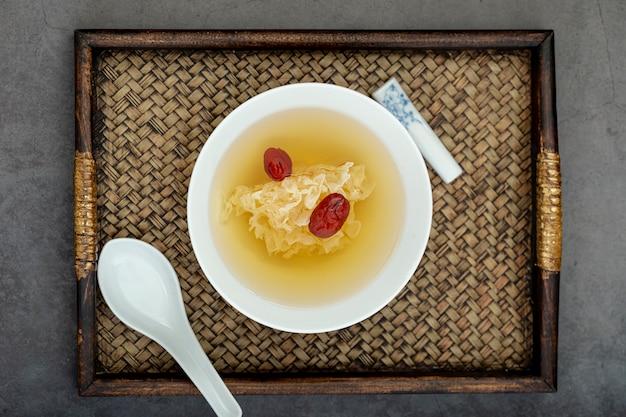 Witte kom met soep op een houten bord