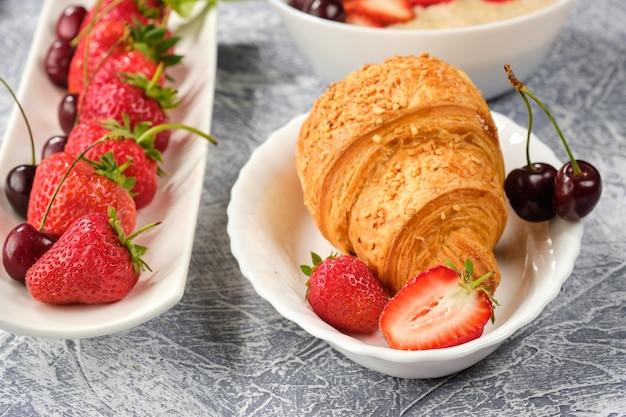 Witte kom pap met aardbeien en kersen, croissants en knäckebröd met kaas en aardbeien