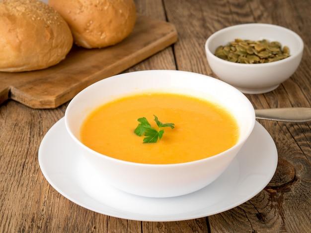 Witte kom pompoen soep, gegarneerd met peterselie op houten achtergrond, zijaanzicht.