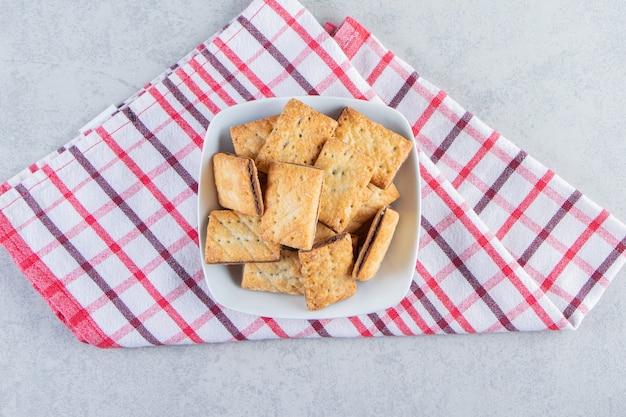 Witte kom smakelijke krokante crackers op stenen achtergrond.