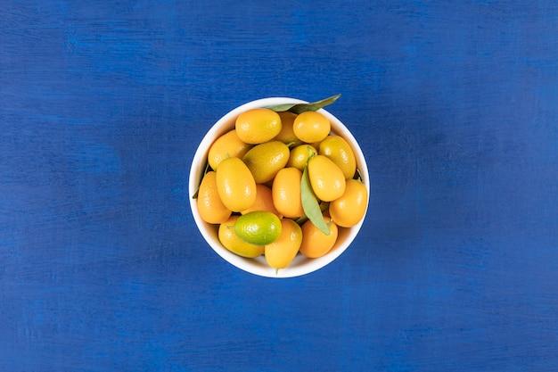 Witte kom vol gele kumquats op blauwe ondergrond.