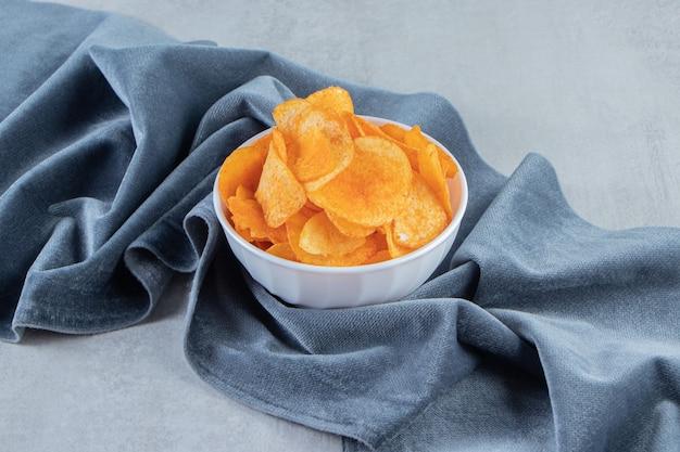 Witte kom vol pittige chips op steen.