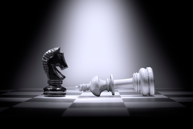 Witte koning schaakstuk verslaan door zwarte ridder schaakstuk