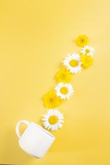 Witte kop en kamille bloemen op een gele achtergrond. bloemen gieten uit een kopje. surrealistische compositie met kamillethee. plat erop gelegd.
