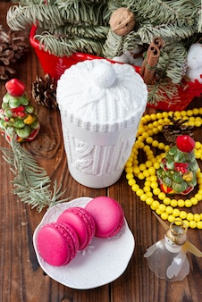 Witte kop en roze makarons met kerstmisdecoratie op houten achtergrond