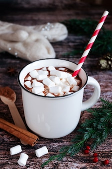 Witte kop hete gekruide cacao of chocolade met marshmallows en een gestreept papieren rietje op een rustiek houten tafelblad