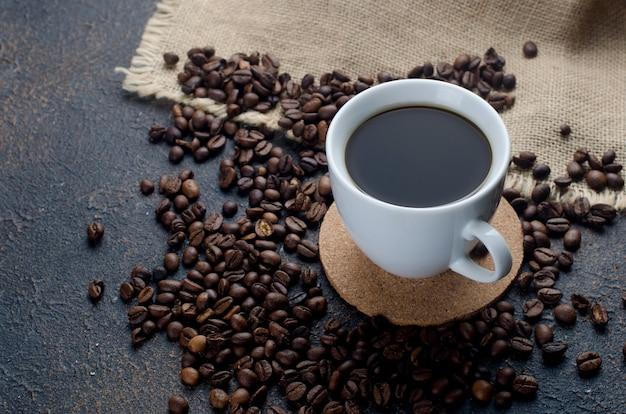Witte kop i zwarte koffie en koffiebonen op donkere betonnen ondergrond. het concept van warme dranken, verkwikkend ontbijt.