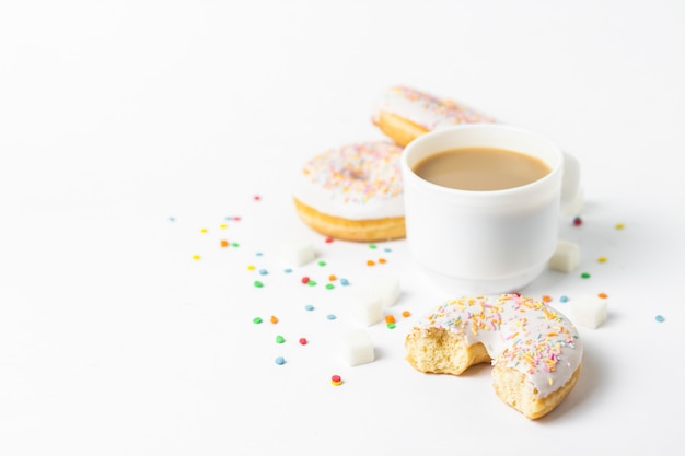Witte kop, koffie of thee met melk en verse smakelijke donuts, zoete veelkleurige decoratieve snoep op een witte achtergrond. bakkerijconcept, vers gebak, heerlijk ontbijt, fast food.