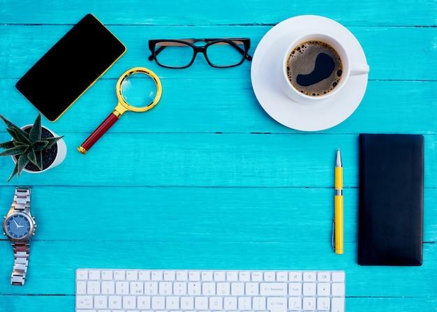 Witte kop koffie, zwarte notebook, telefoon, bloem, vergrootglas, gele pen, horloge en wit toetsenbord