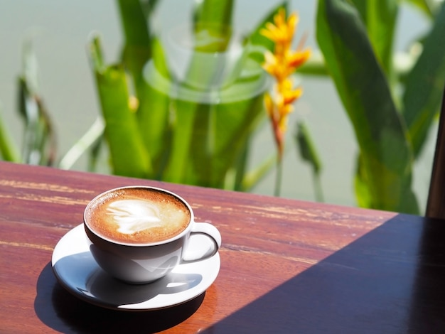 Witte kop koffiecappuccino op houten lijst naast glasvenster