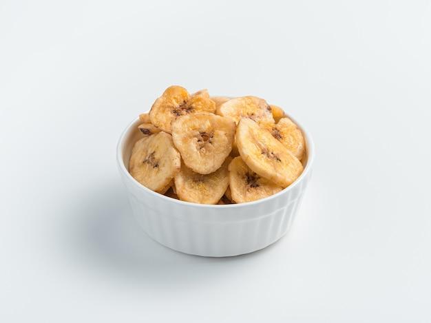 Witte kop met bananenchips op een lichte achtergrond