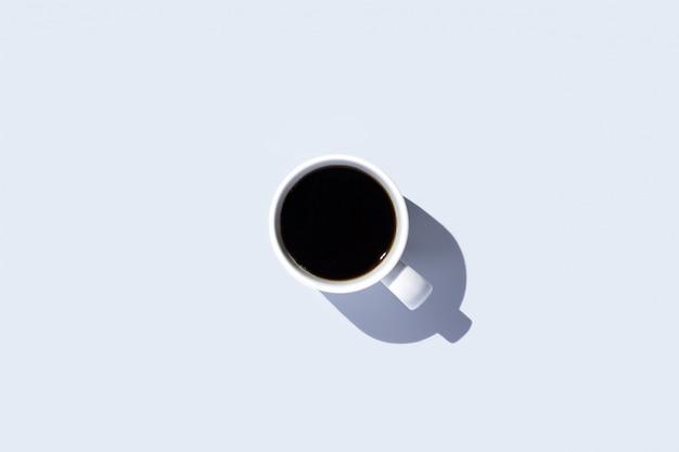 Witte kop met een kopje koffie op een geïsoleerde lichte ruimte. bovenaanzicht, plat lag