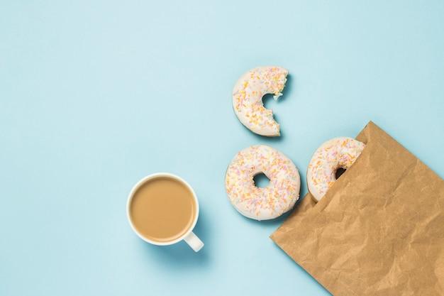 Witte kop met koffie of thee en papieren zak met verse heerlijke zoete donuts op een blauwe achtergrond. concept van fast food, bakkerij, ontbijt, snoep. minimalisme. plat lag, bovenaanzicht.