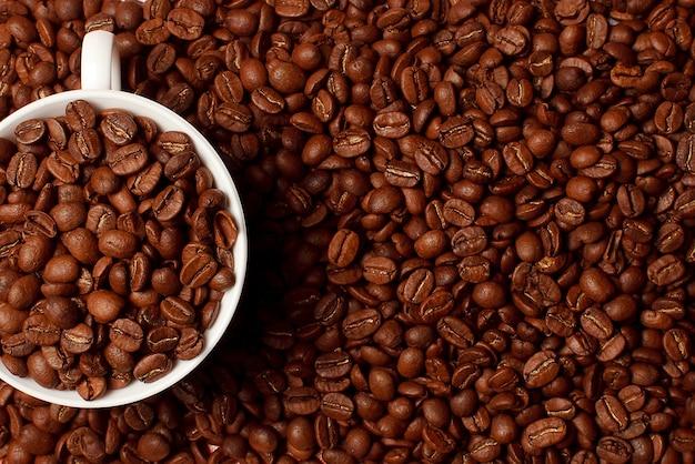 Witte kop met koffiebonen. koffie in bonenmacro. abstracte textuur als achtergrond. de textuur van koffiebonen. voedselachtergrond van koffiebonen