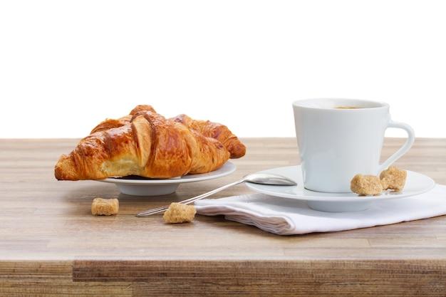 Witte kop met verse espressokoffie en croissant