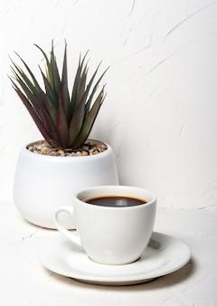 Witte kop met zwarte aromatische koffie op een witte abstracte achtergrond met een ingemaakte bloem op de achtergrond.