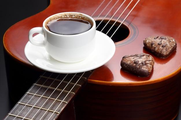 Witte kop met zwarte koffie en koekjes die op de akoestische gitaar liggen