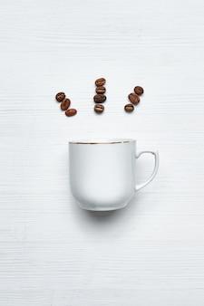 Witte kop op een houten achtergrond met abstracte stralen van koffiebonen. detailopname. bovenaanzicht