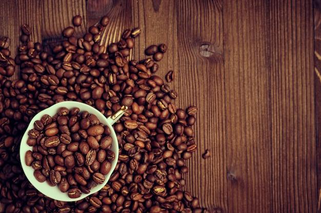 Witte kop op gebrande koffiebonen en een verbrande houten bord. kopieer ruimte. afgezwakt.