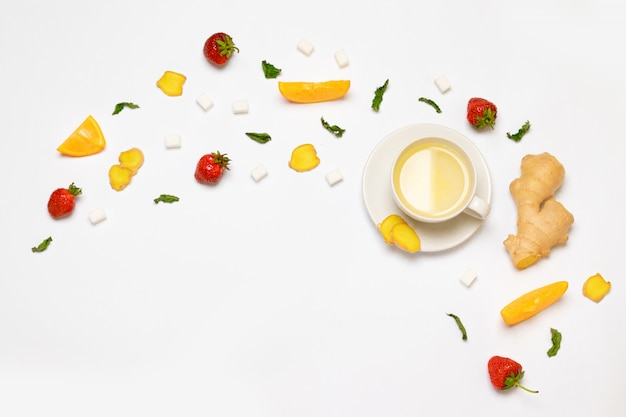 Witte kop thee en verse aardbeien, stukjes gember, sinaasappel, munt en suiker