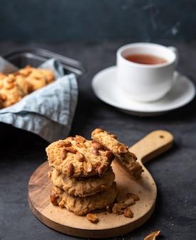 Witte kop thee met de koekjes met de hand gemaakte dichte omhooggaand van de waterstroom