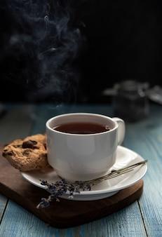 Witte kop thee met met de hand gemaakte dichte omhoog grijs van de waterstroomkoekjes