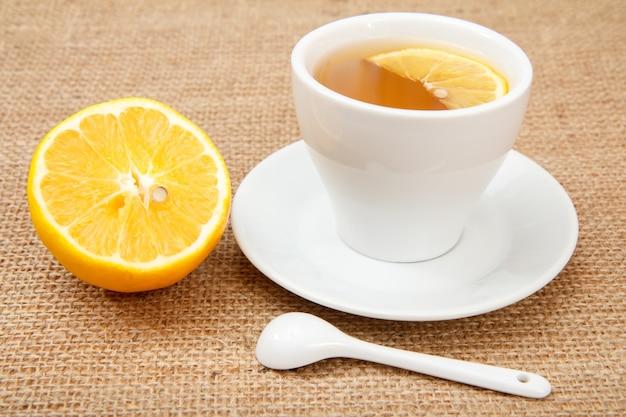 Witte kop thee met schotel, lepel en een stuk citroen op zakachtergrond