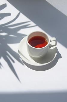 Witte kop van zwarte thee met palmboomschaduw