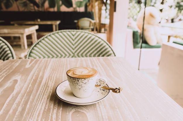 Witte kop warme cappuccino op houten lichte tafel achtergrond. ontbijt tijd