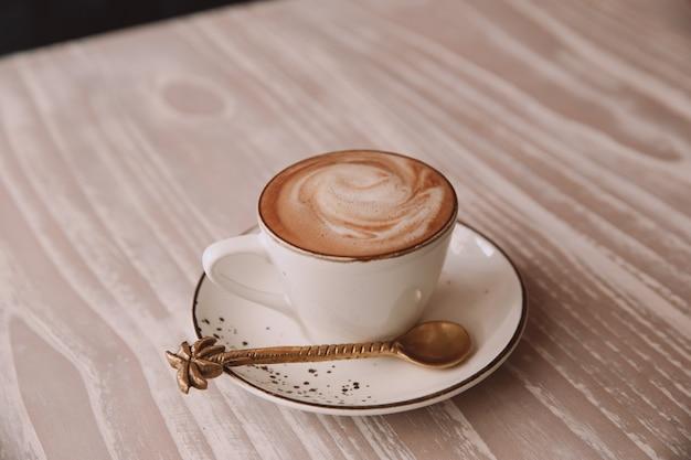 Witte kop warme cappuccino op houten lichte tafel achtergrond.