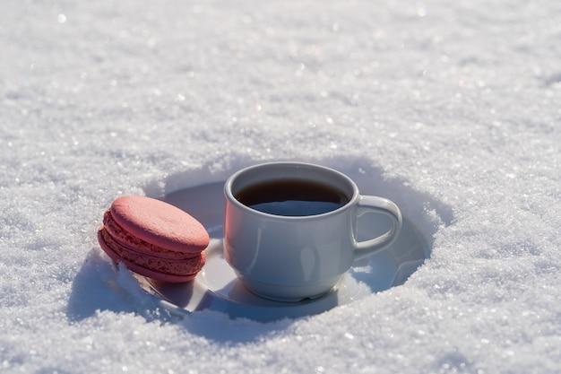 Witte kop warme koffie met roze macaron op een bedje van sneeuw en witte achtergrond, close-up. concept van kerst winterochtend