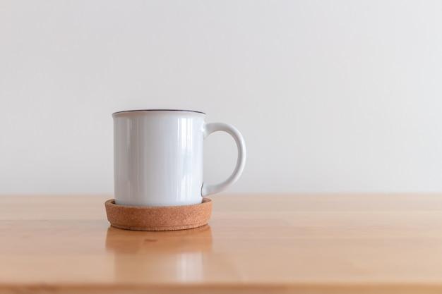 Witte kop warme koffiemok op houten tafel met witte achtergrond.